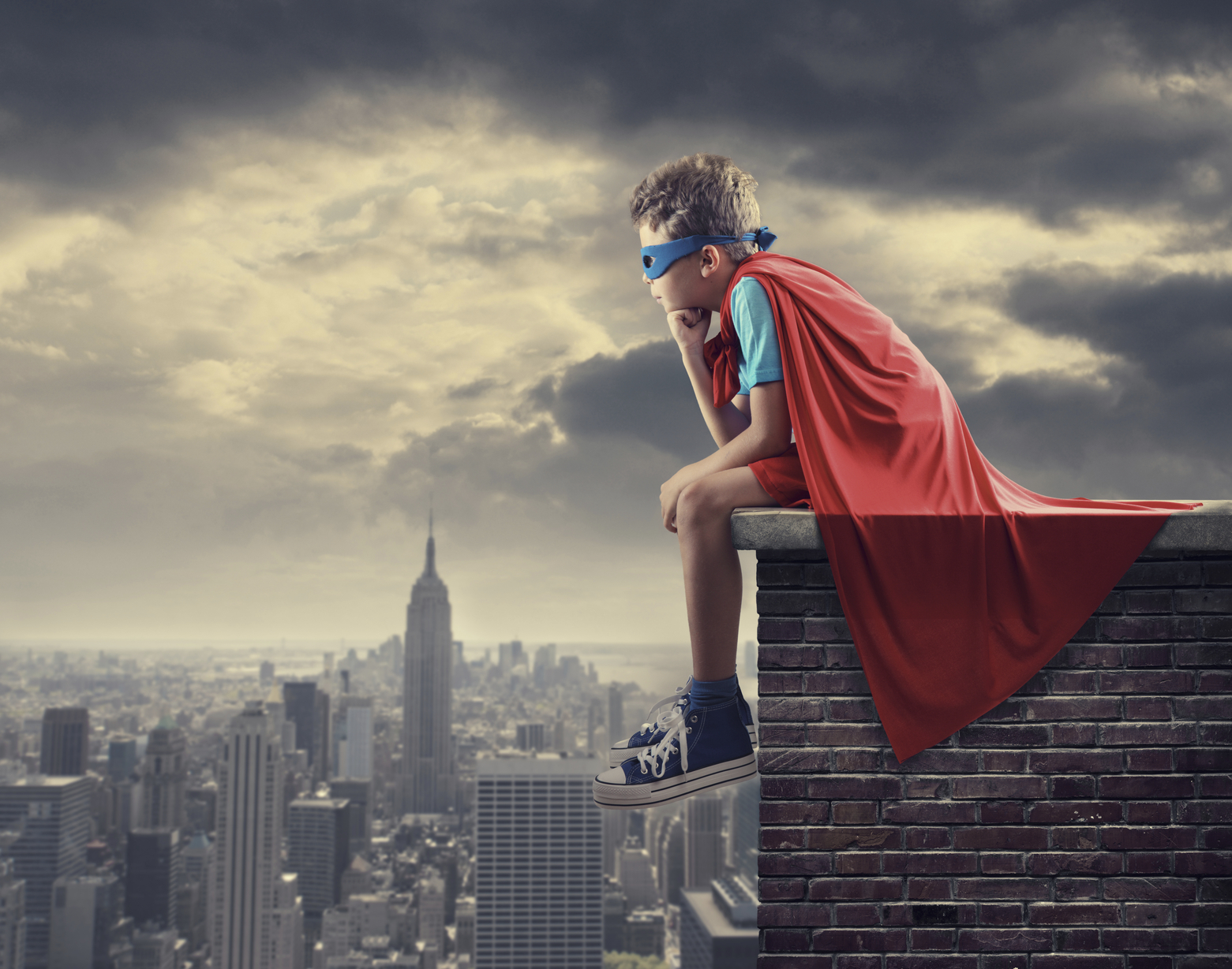 Little superhero sitting on top of wall
